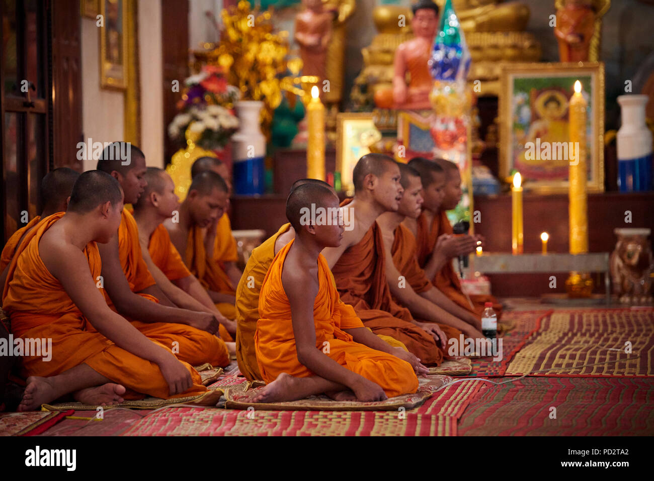 A group of young Buddhist monks sitting on the ground during a ceremony in one of the shrines in their monastery. In Siem Reap, Cambodia. - Stock Image