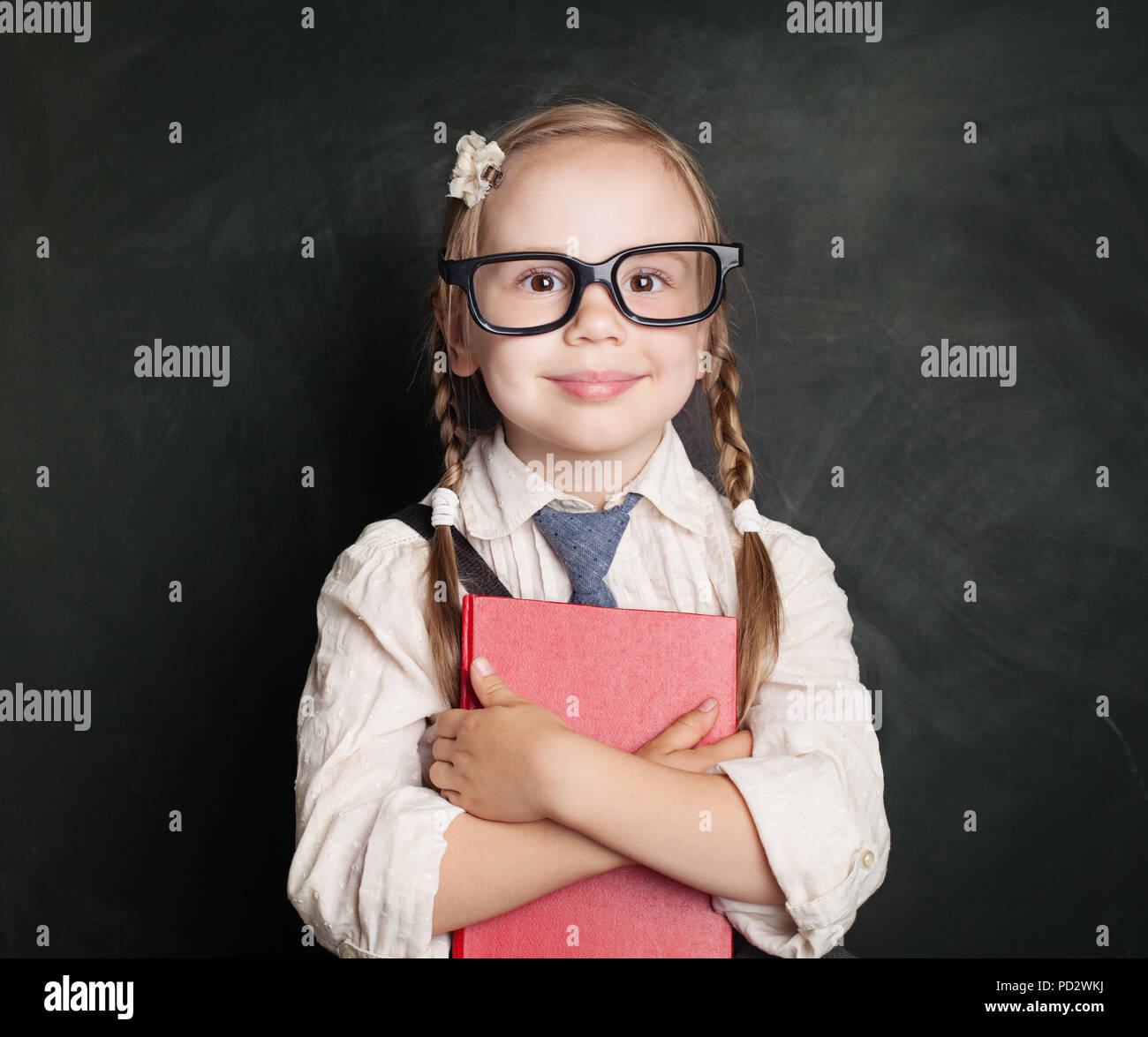 d4a2ed8111f2 Child with book. Small schoolgirl in uniform clothes holding book and  smiling against green chalk board background. Back to school, children  learning