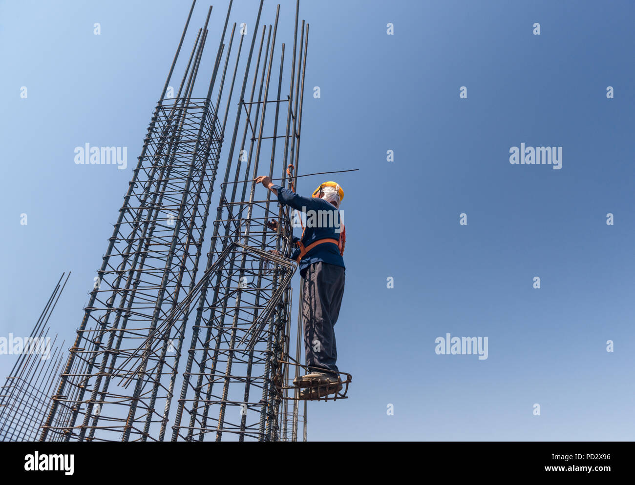 worker at altitude strengthens the pillars from rebar, on the blue ...