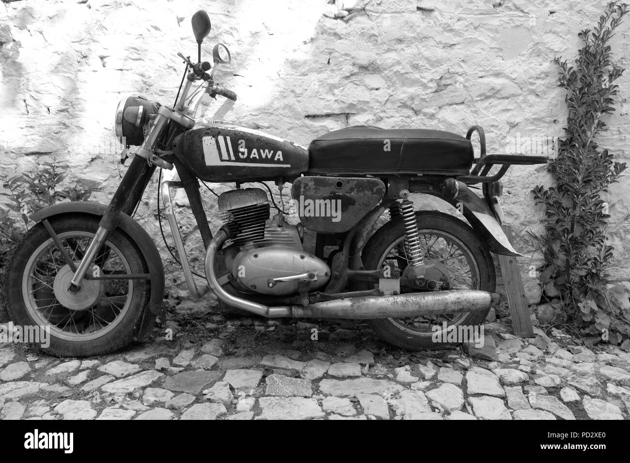 Black white monochrome shot of classic vintage czech jawa motorbike parked on cobblestone street against a white wall in albania