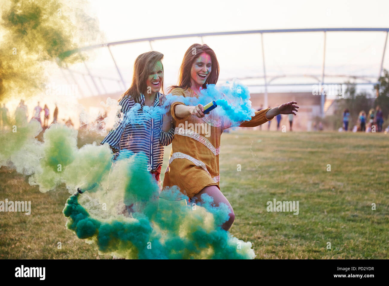 Two young women dancing with coloured smoke bombs at Holi Festival - Stock Image