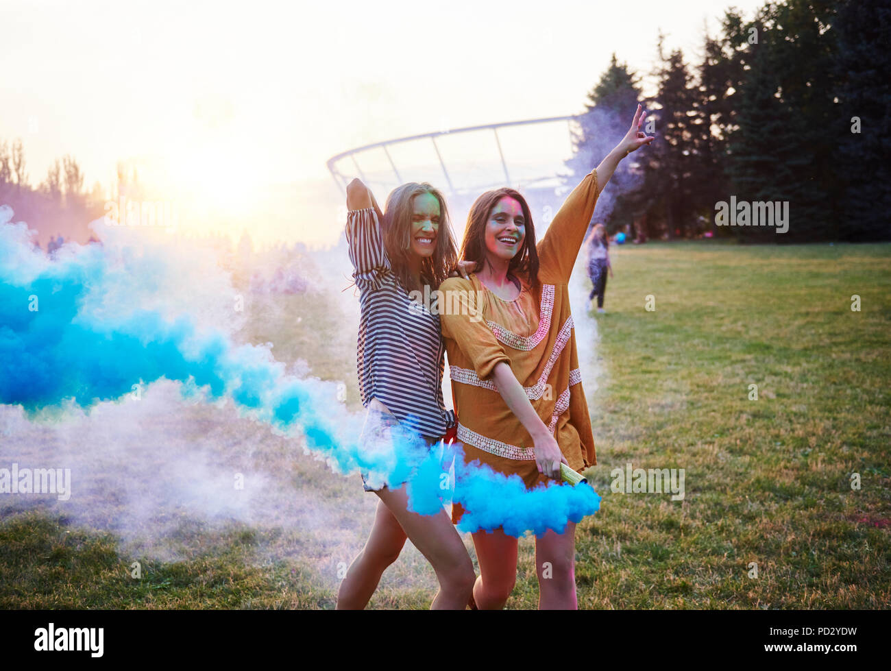 Two young women dancing with blue smoke bombs at Holi Festival - Stock Image