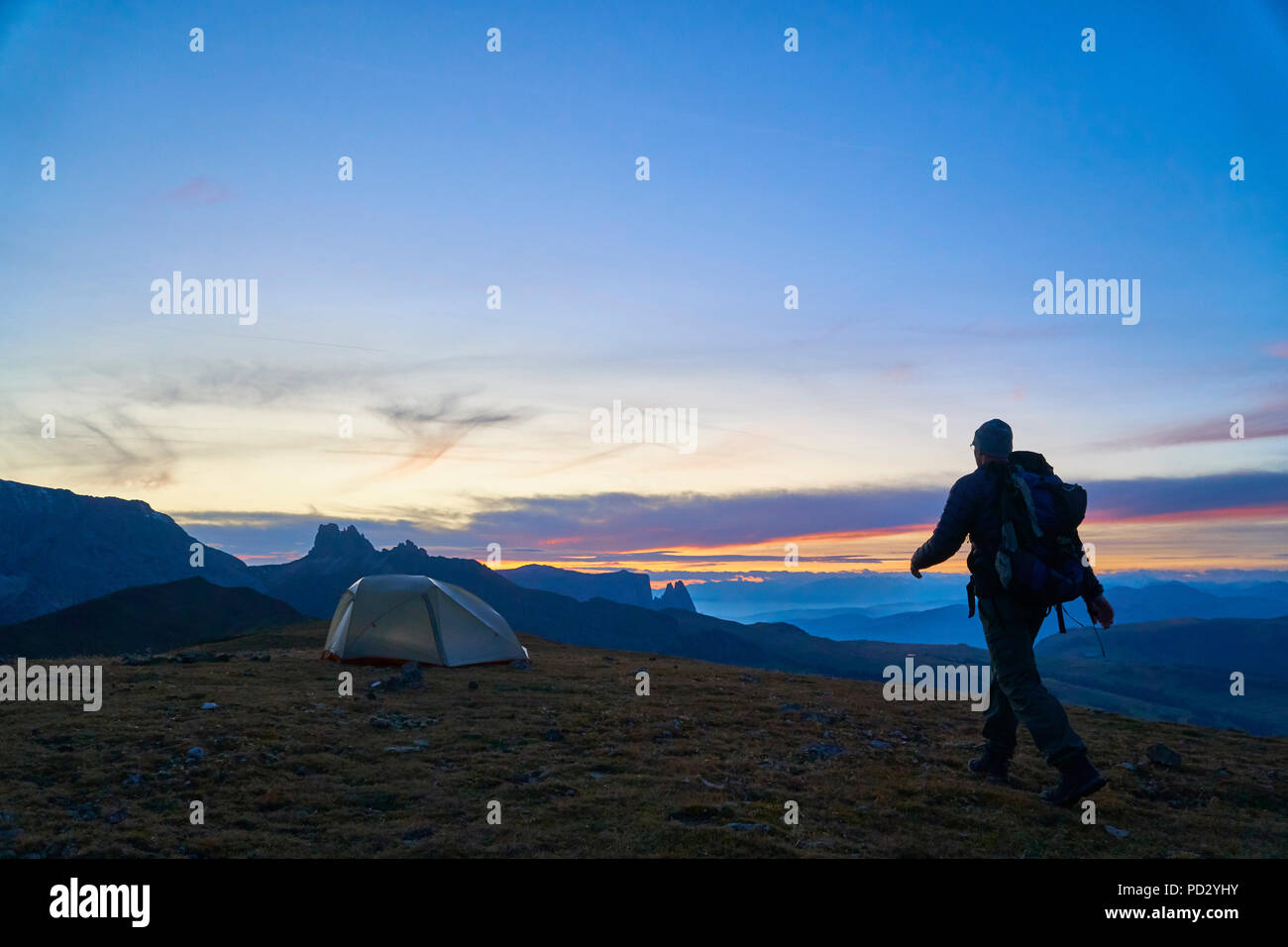 Hiker walking to his tent at sunset, Canazei, Trentino-Alto Adige, Italy - Stock Image