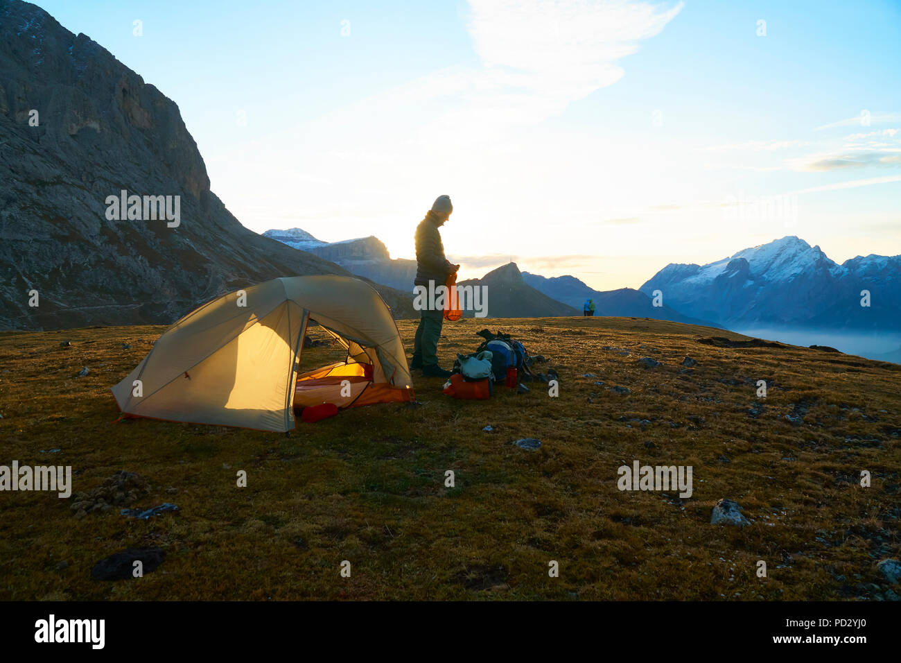 Hiker by tent at sunset, Canazei, Trentino-Alto Adige, Italy - Stock Image