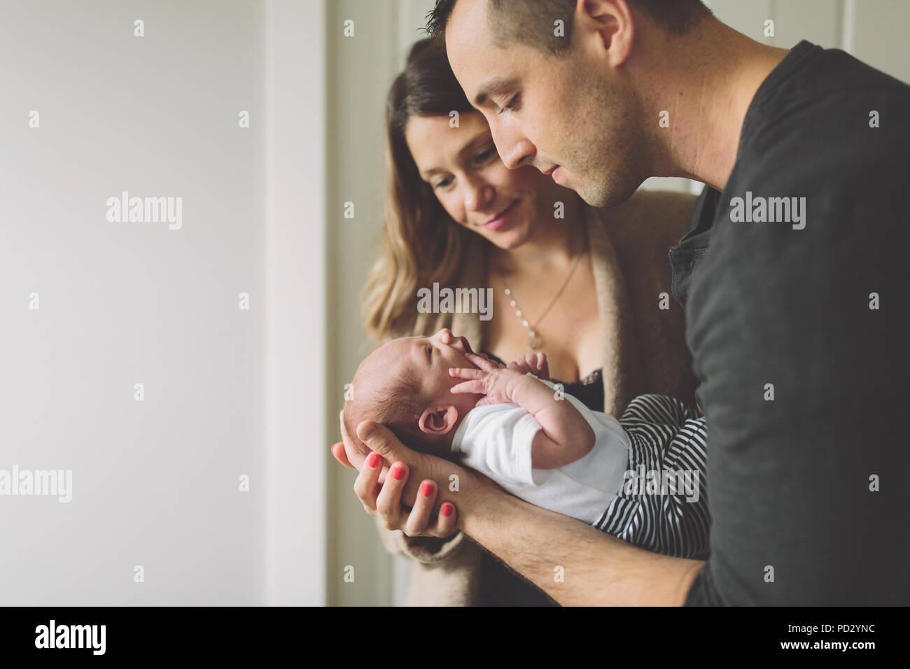 New parents admiring new born baby boy - Stock Image