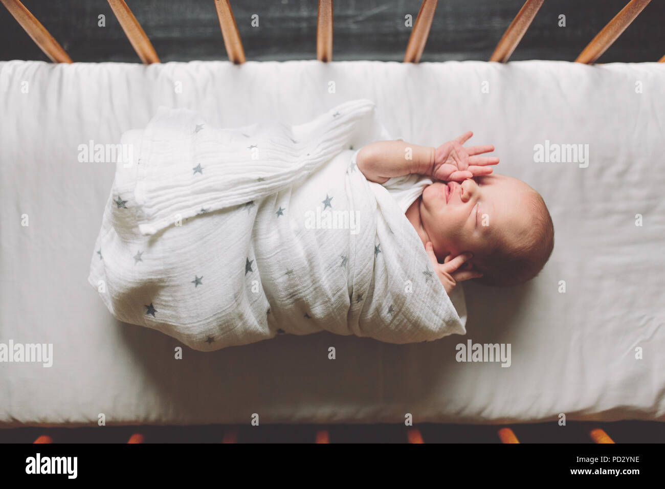 New born baby boy swaddled in cot, overhead view - Stock Image