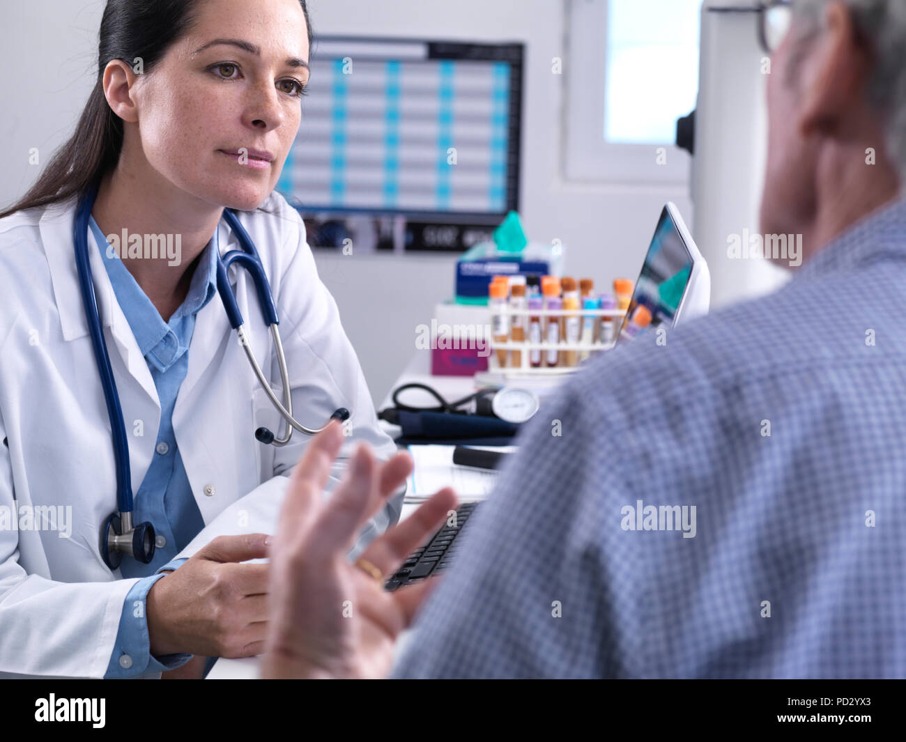 Doctor listening to a patients concerns during a check up in the clinic - Stock Image