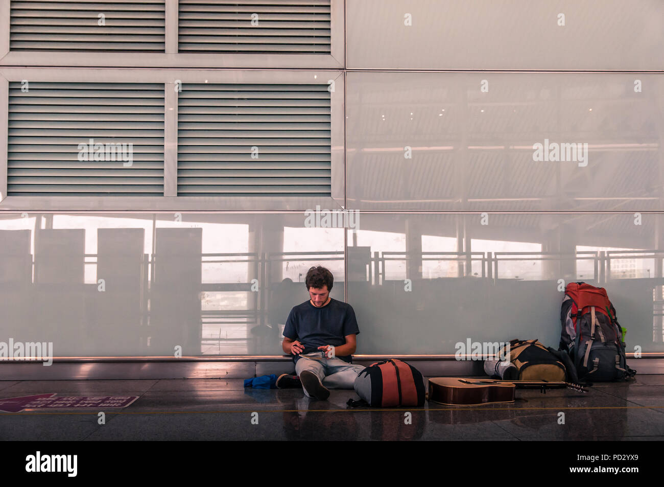 Traveller on airport floor, Guangzhou, Jiangxi, China - Stock Image