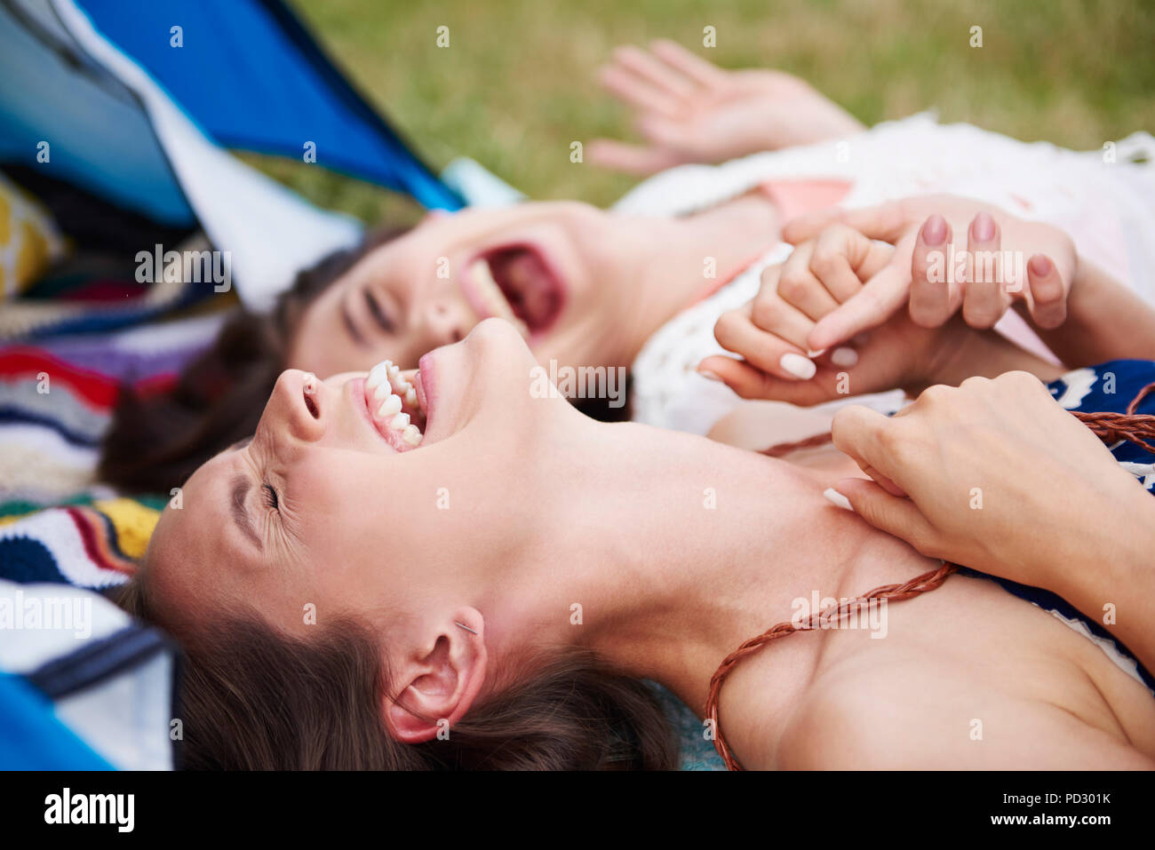 Friends lying on ground, laughing and enjoying music festival - Stock Image