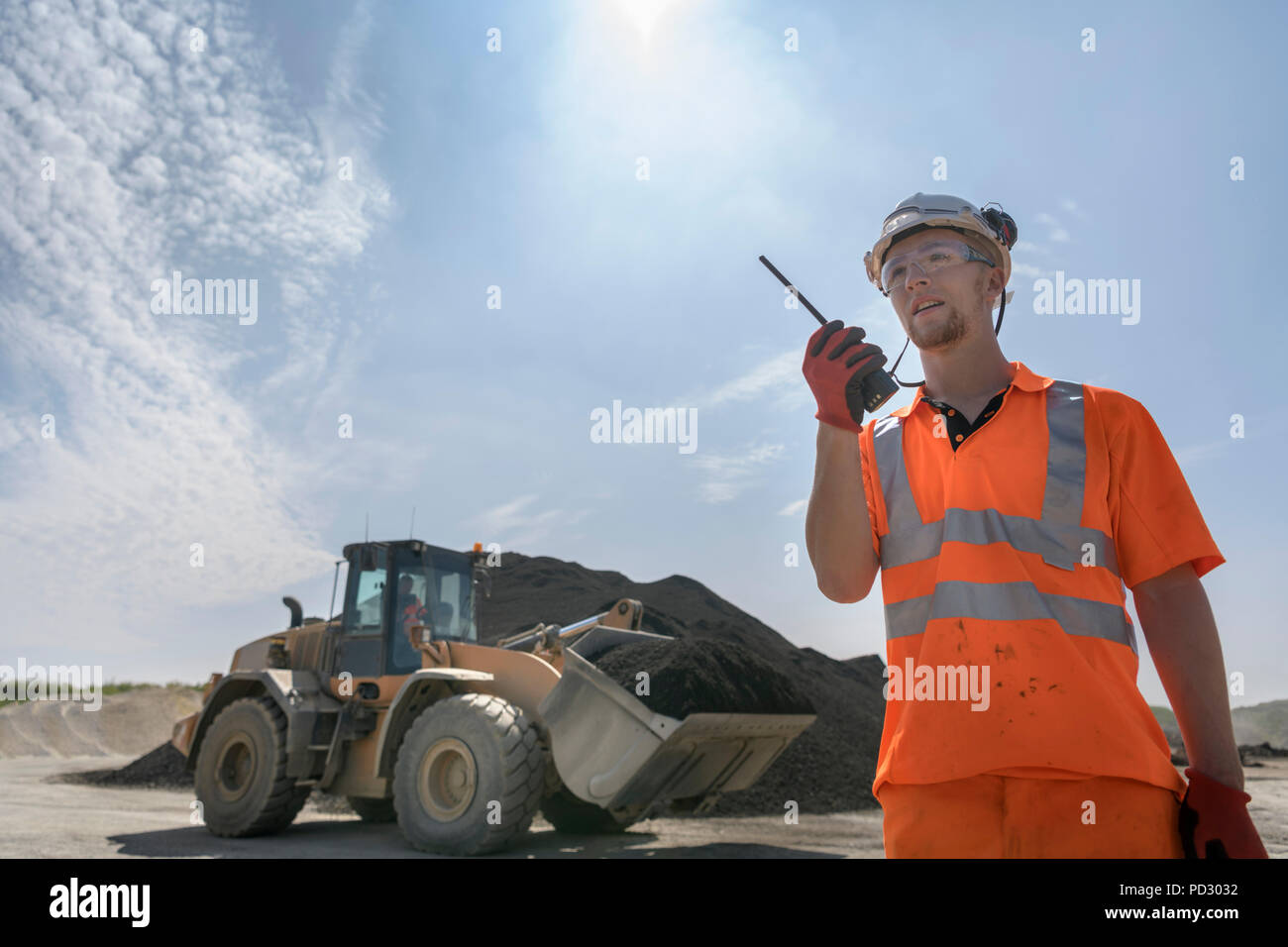 Worker communicating via walkie talkie in front of digger in concrete recycling site - Stock Image