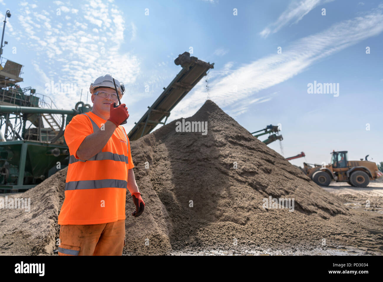 Worker talking on walkie talkie with crusher and concrete screening machine in concrete recycling site - Stock Image