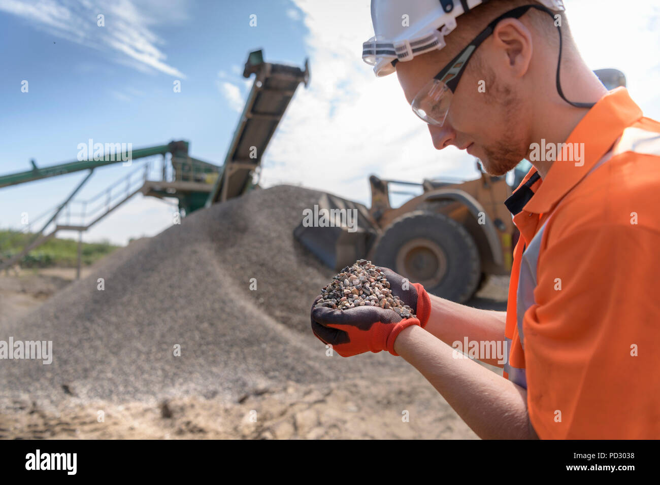 Worker checking handful of screened concrete in concrete recycling site - Stock Image