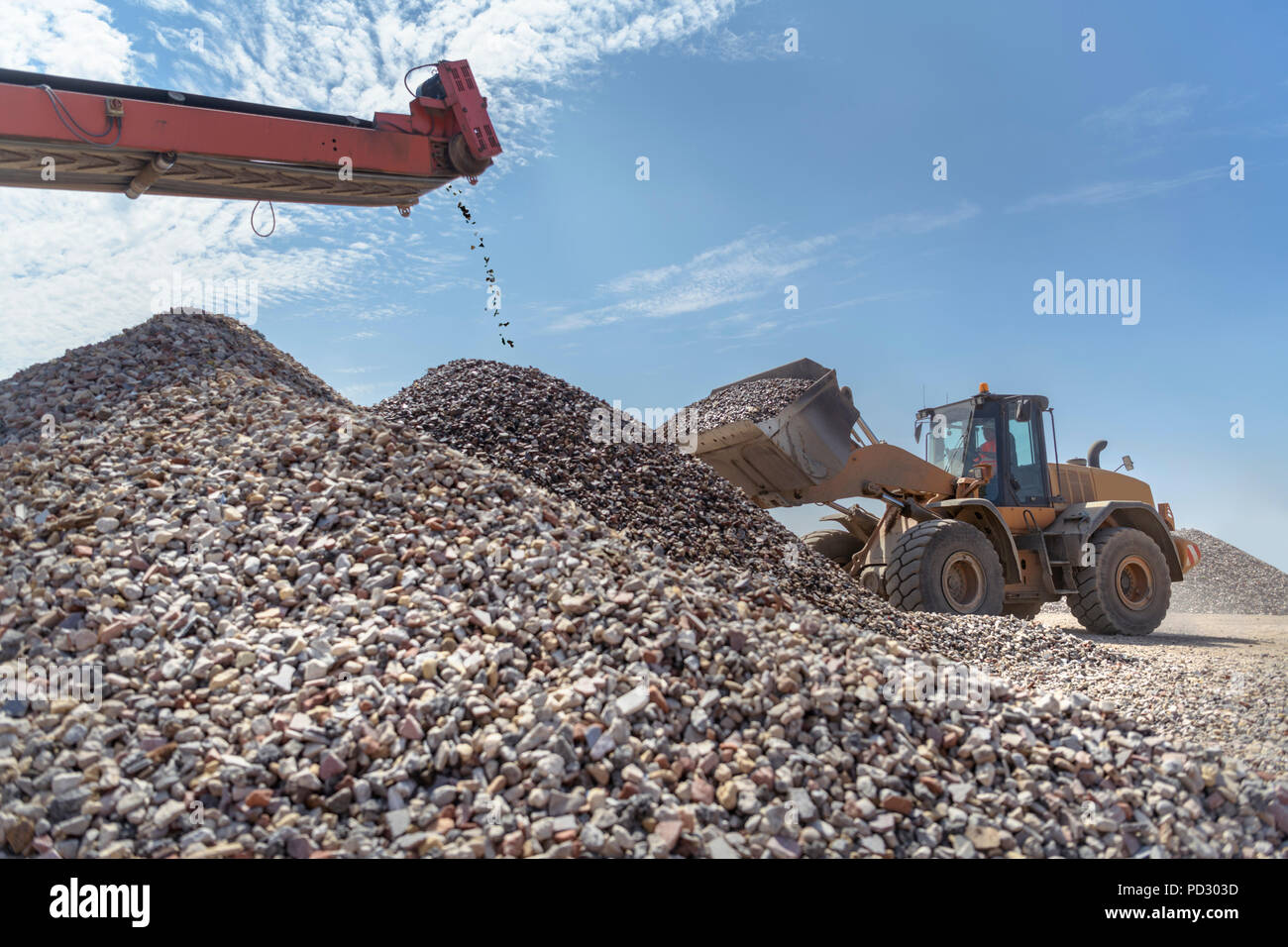 Digger with screened and crushed concrete in concrete recycling site - Stock Image