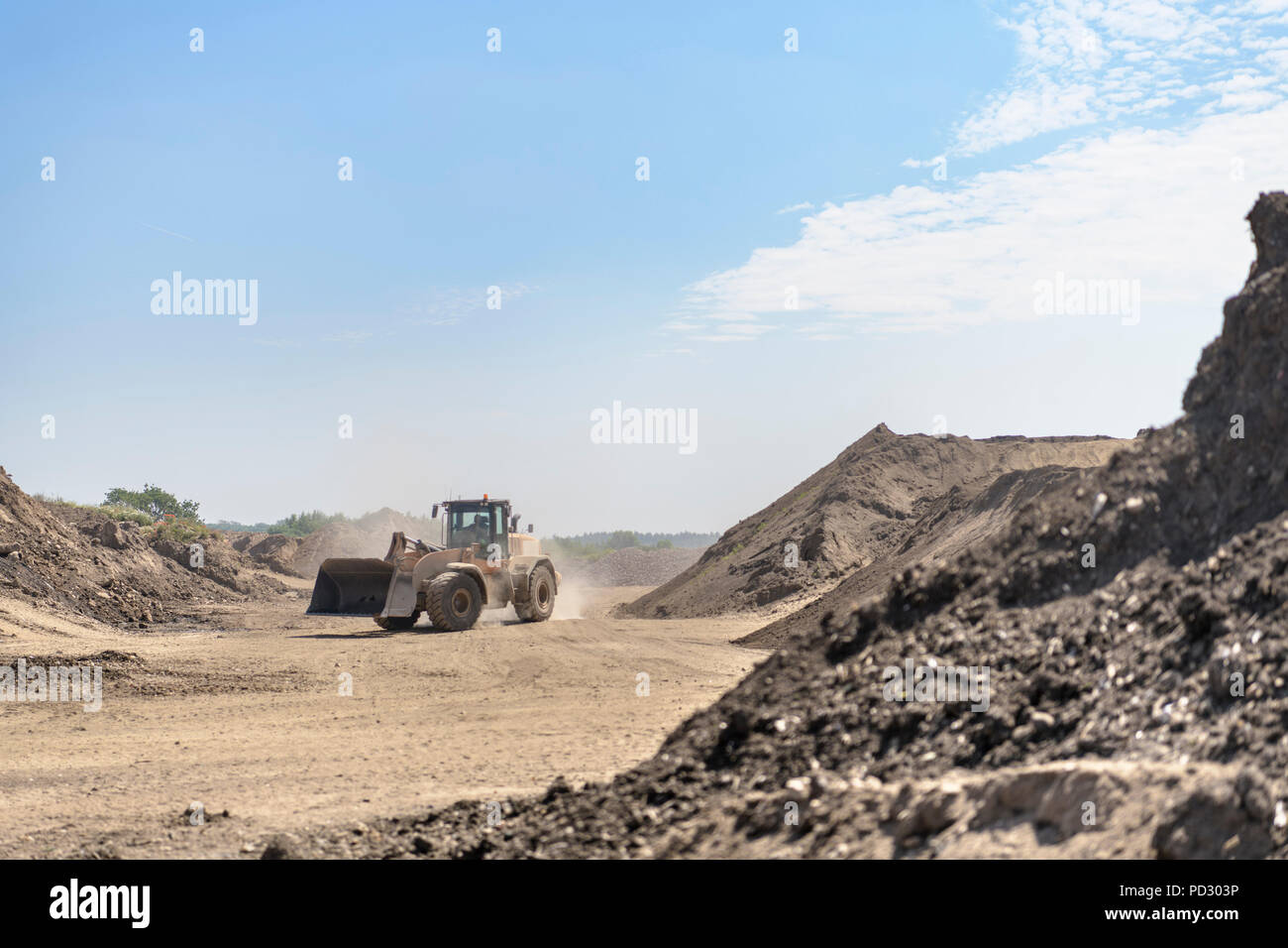 Digger on the move in distance in concrete recycling site - Stock Image