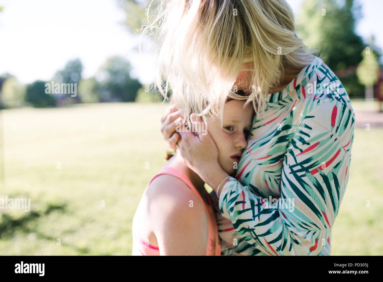 Mother consoling daughter in park - Stock Image