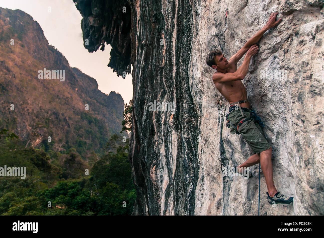 Man sport climbing on limestone, Thakhek, Laos - Stock Image