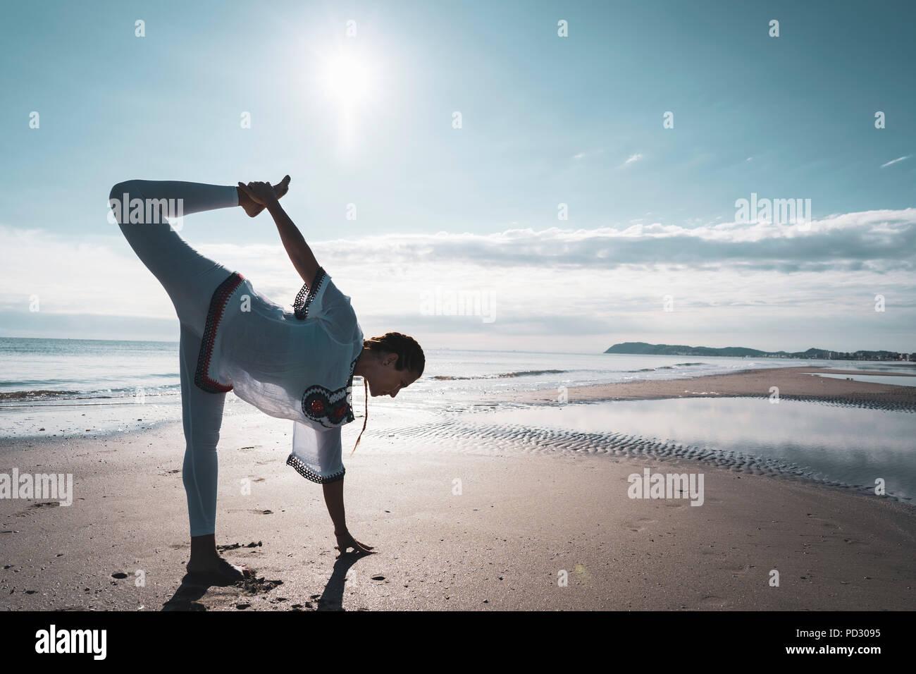 Woman practising yoga on beach - Stock Image