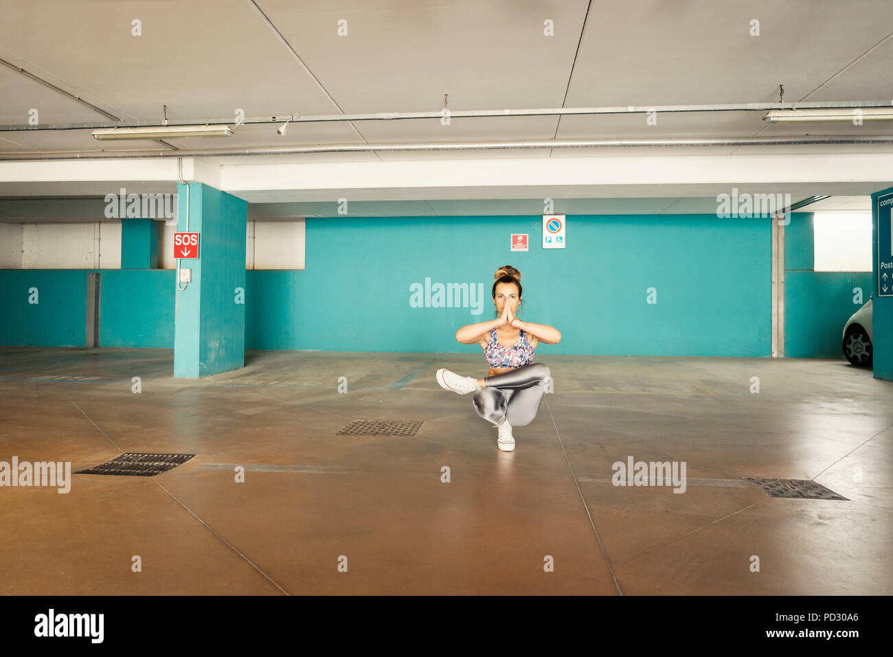 Woman practising yoga in parking lot - Stock Image