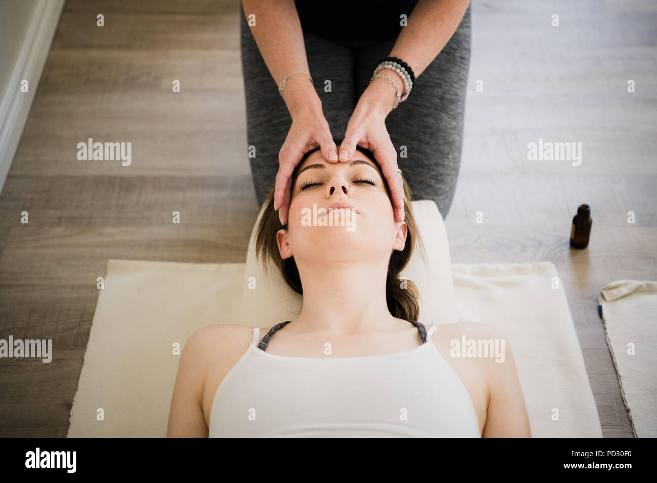 Woman enjoying head massage in yoga retreat Stock Photo