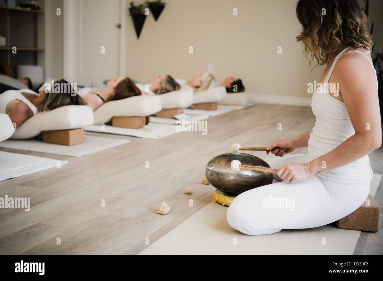 Women in relaxation pose after yoga class at retreat - Stock Image