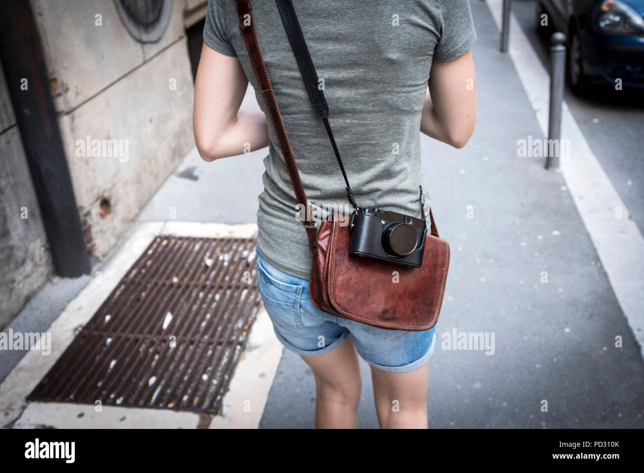 Young woman with leather handbag and retro camera walking - Stock Image