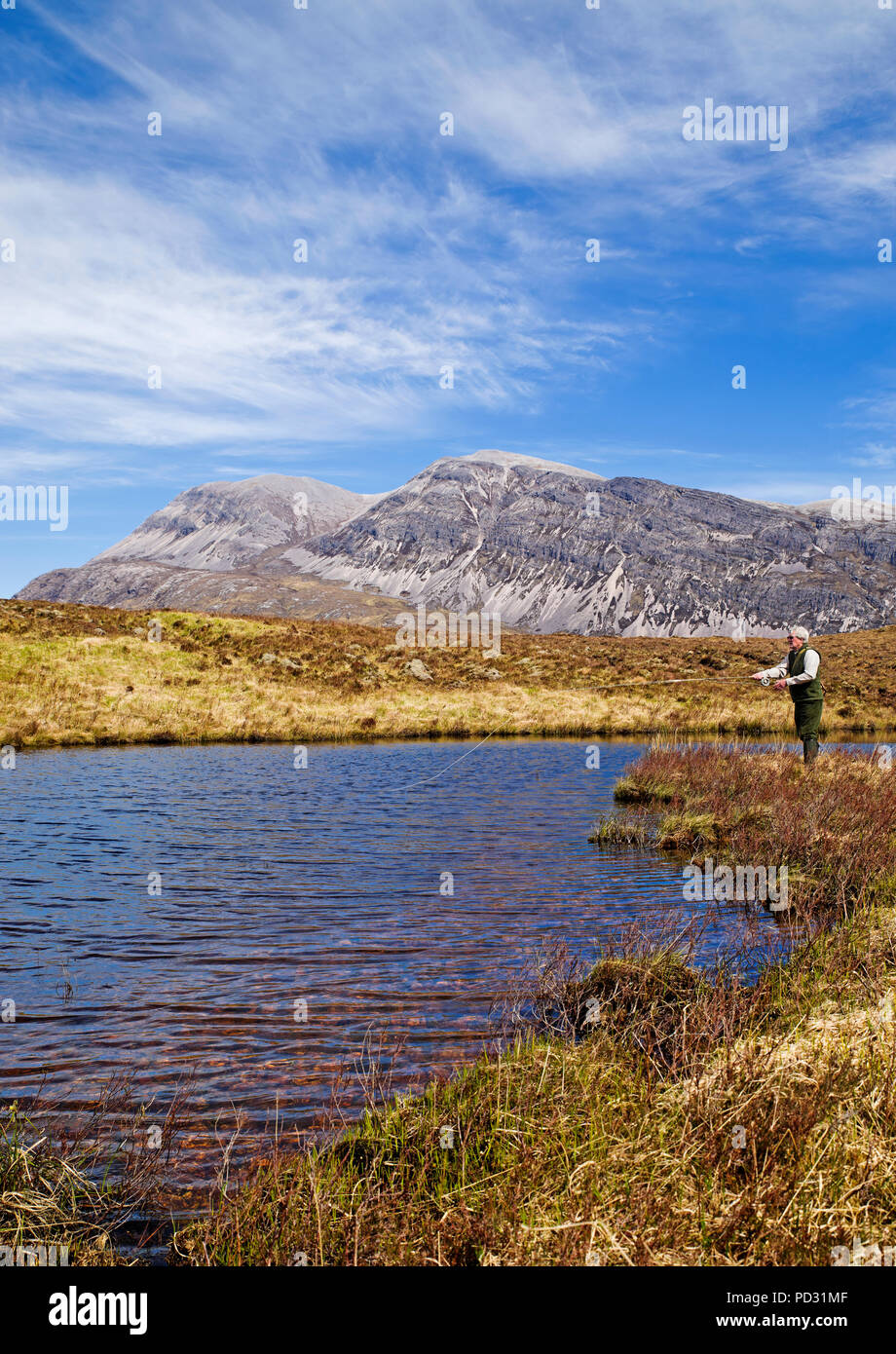 Angler fishing for wild brown trout on remote hill loch on Reay Forest Estate, Arkle in background, Sutherland, Scottish Highlands, Scotland UK. - Stock Image