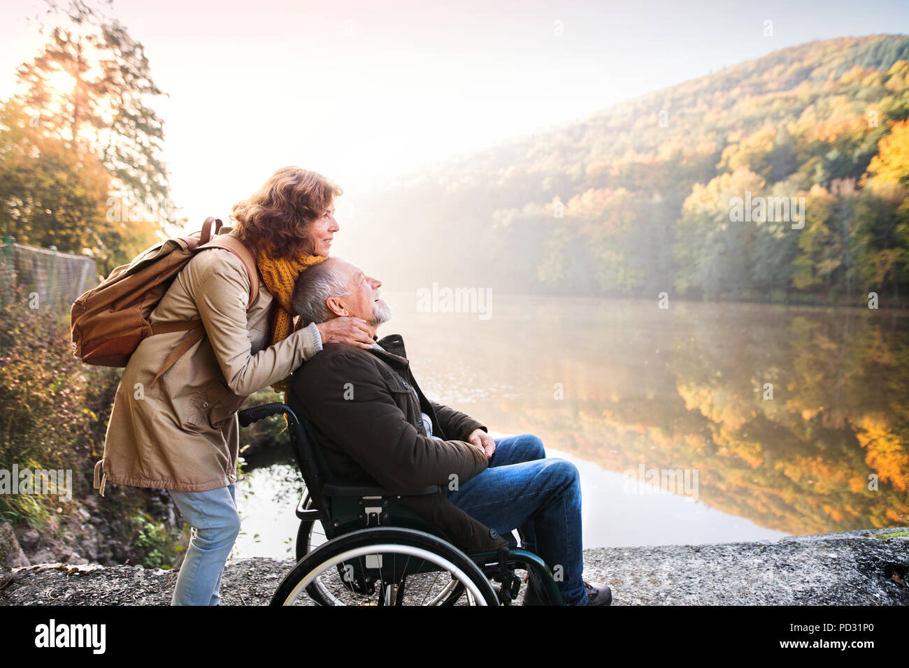 Senior couple with wheelchair in autumn nature. - Stock Image