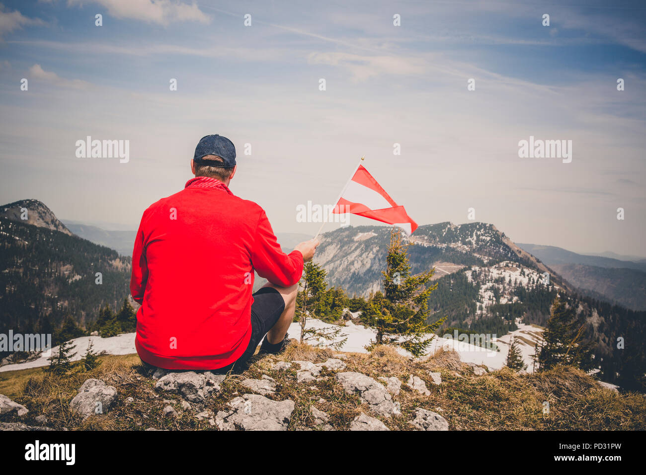 hiker with red sweater is holding an austria flag in the mountains - Stock Image