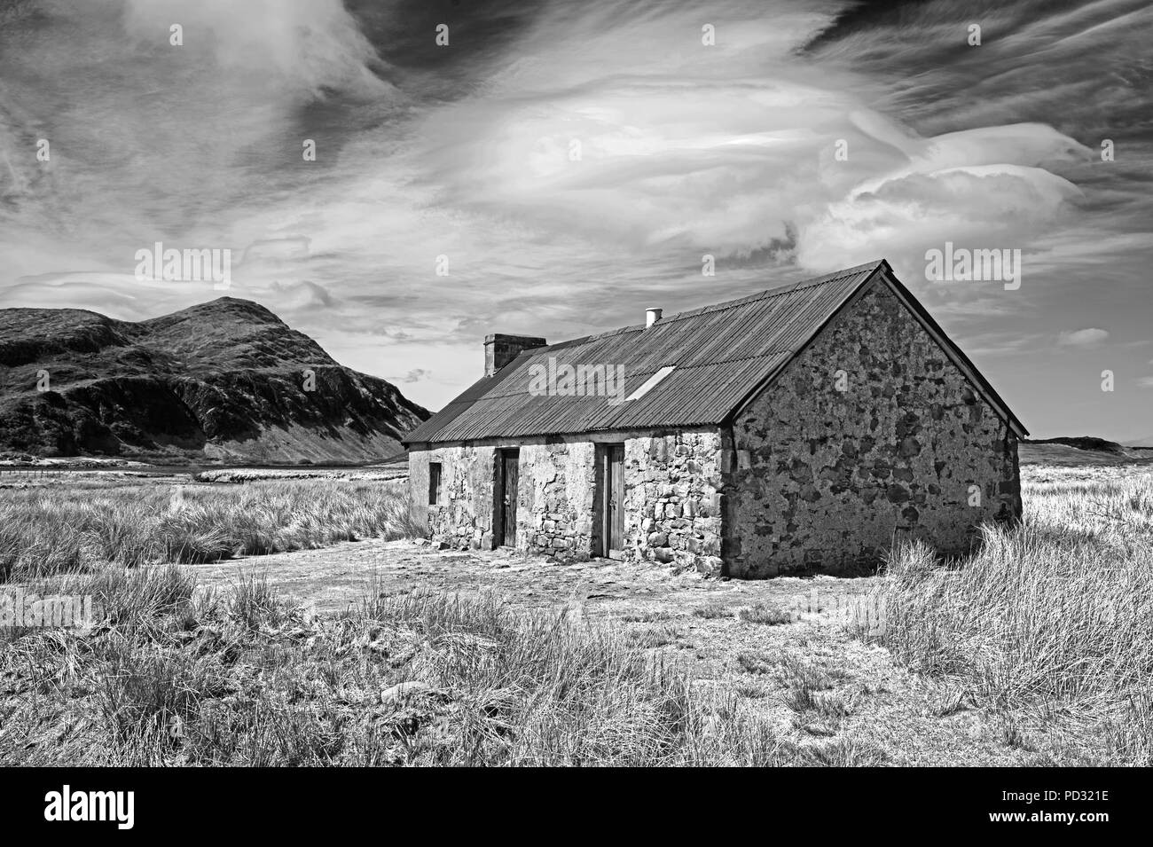 Old traditional hut in remote moorland location, Sutherland, Scottish Highlands, mountain Ben stack in the background, Scotland UK. - Stock Image