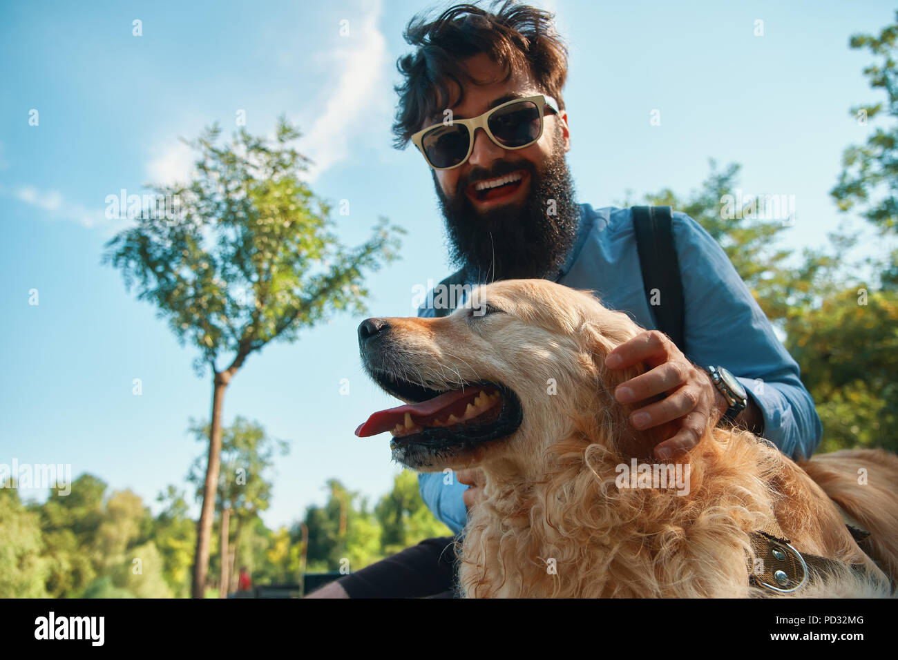 Man and dog having fun, playing, making funny faces while restin Stock Photo