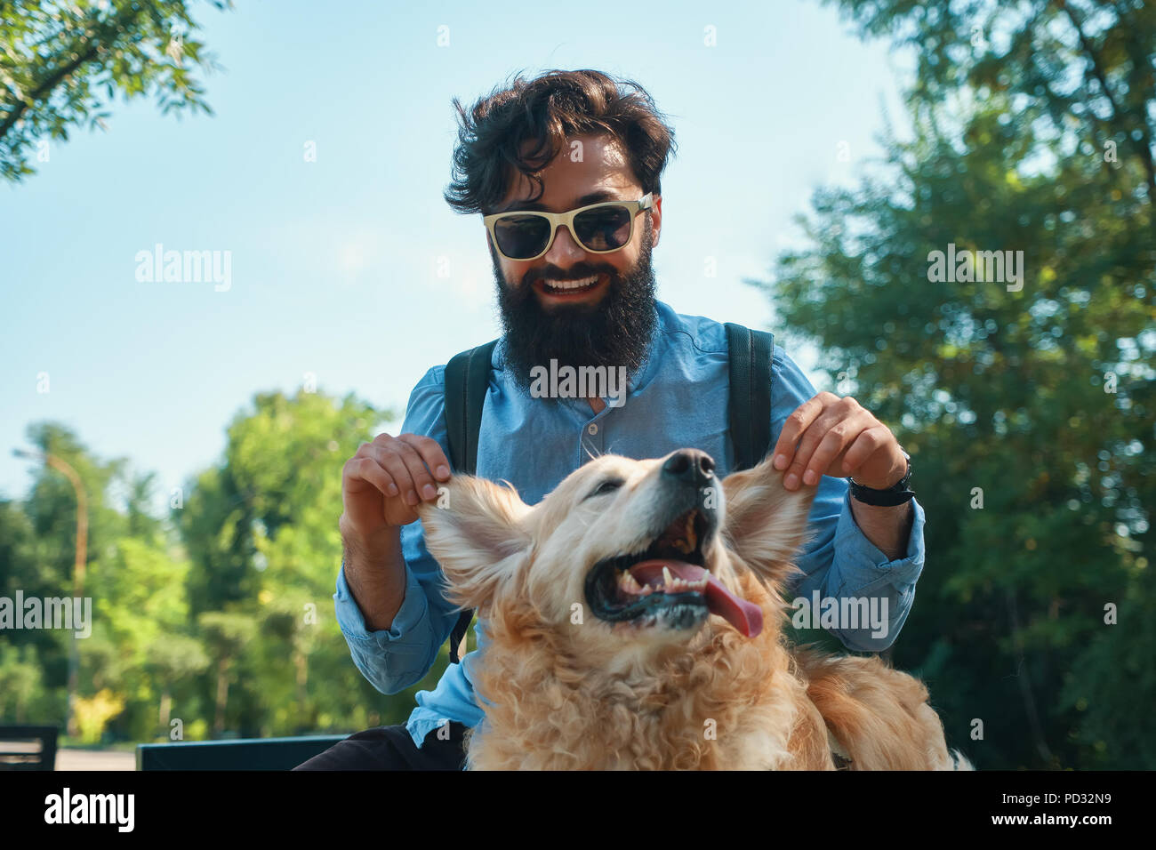 Man and dog having fun, playing, making funny faces while restin - Stock Image