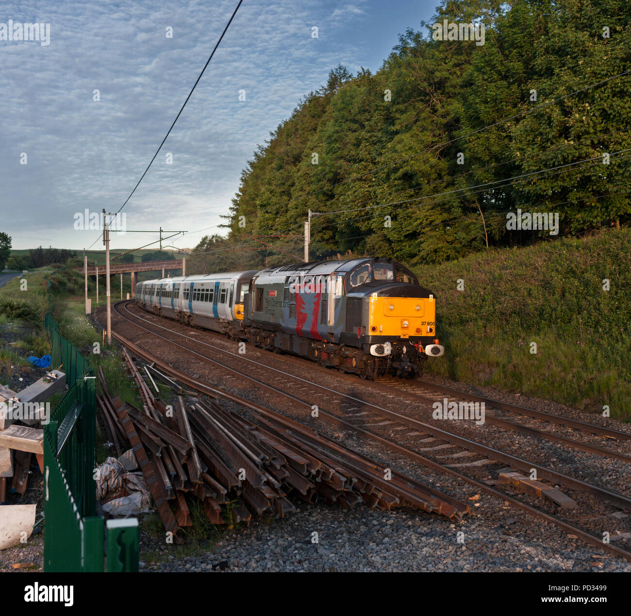 A Europhoenix  class 37 locomotive operated by Rail Operations group at Cowperthwaite (north of Oxenholme) hauling an electric train to Scotland - Stock Image