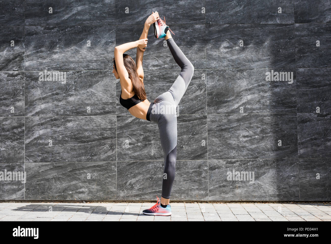Young fitness woman doing warm-up exercise before running stretching her leg by performing knee to chest stretch on the city street. Sporty athlete pr - Stock Image