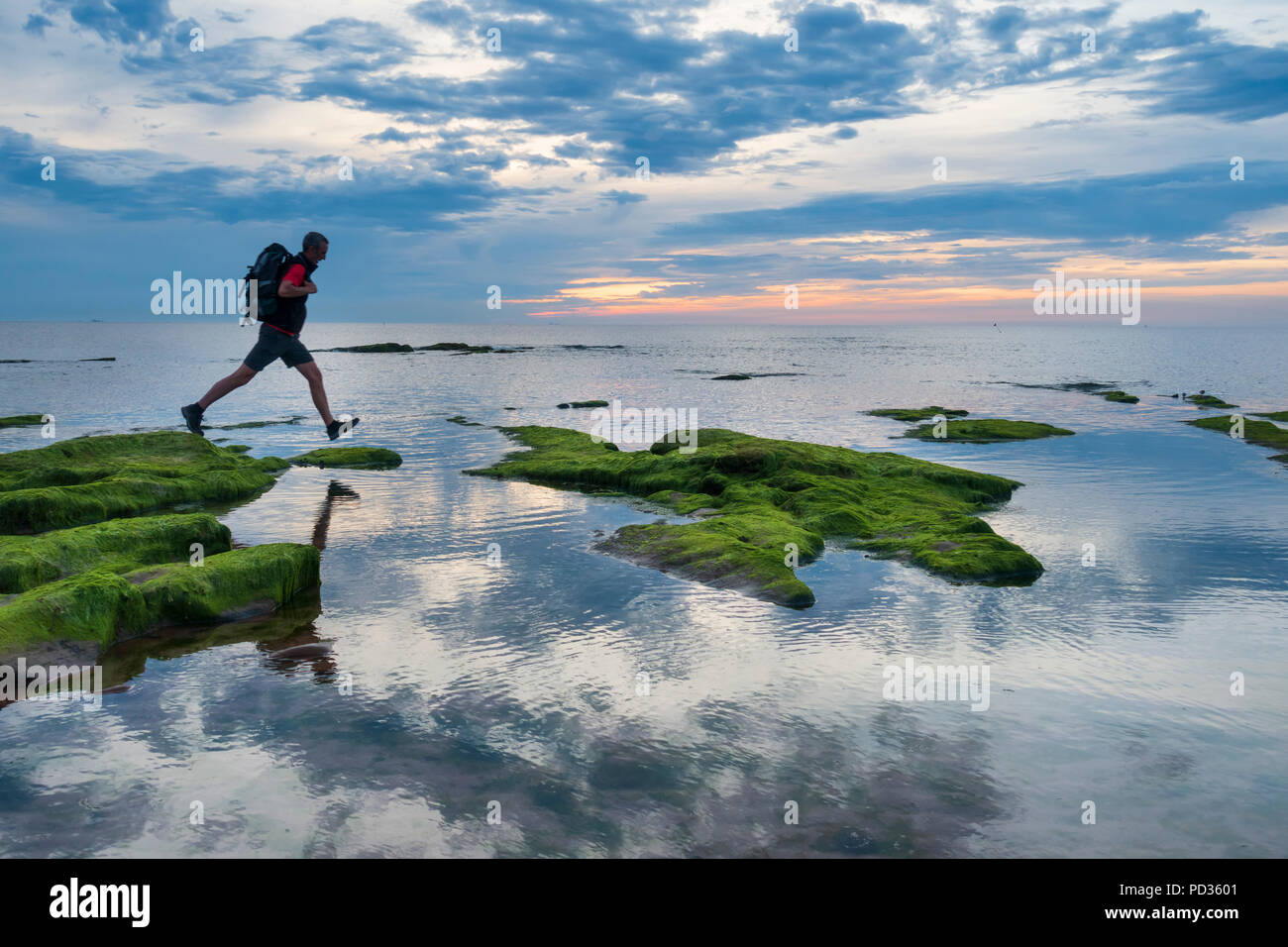 Seaton Carew, County Durham, England. United Kingdom. 6th August, 2018. UK weather: Hazy sunshine at sunrise for an early morning walker on the' England Coast Path' at Seaton Carew on the north east coast on Monday morning. Cooler weather from midweek is forecast, with the possibility of rain. Credit: ALAN DAWSON/Alamy Live News - Stock Image