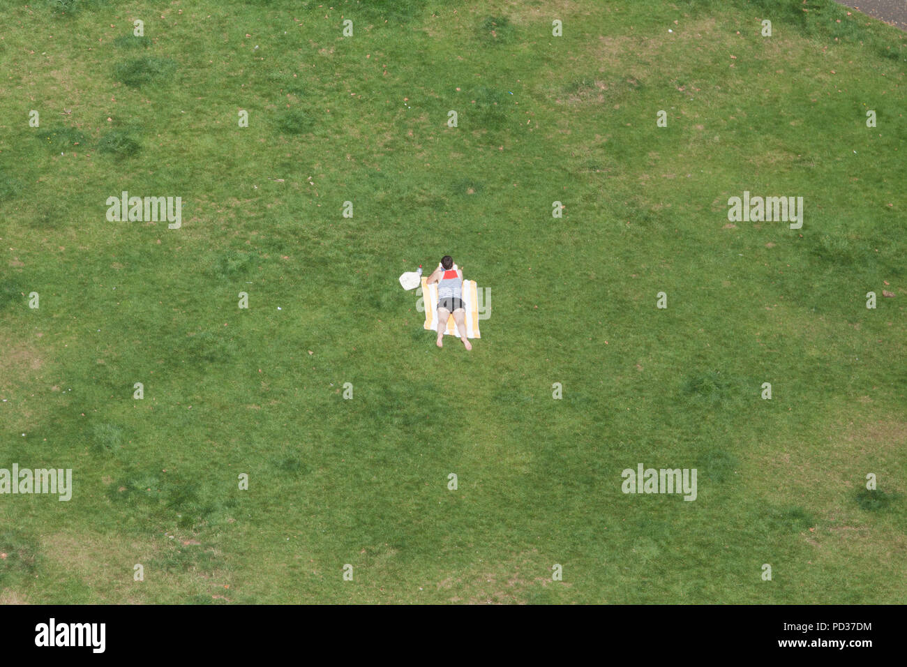 London UK. 6 August  2018. High angle view of a sunbather in a small park in Southwark on another hot day as temperatures are expected to exceed 30C Credit: amer ghazzal/Alamy Live News - Stock Image