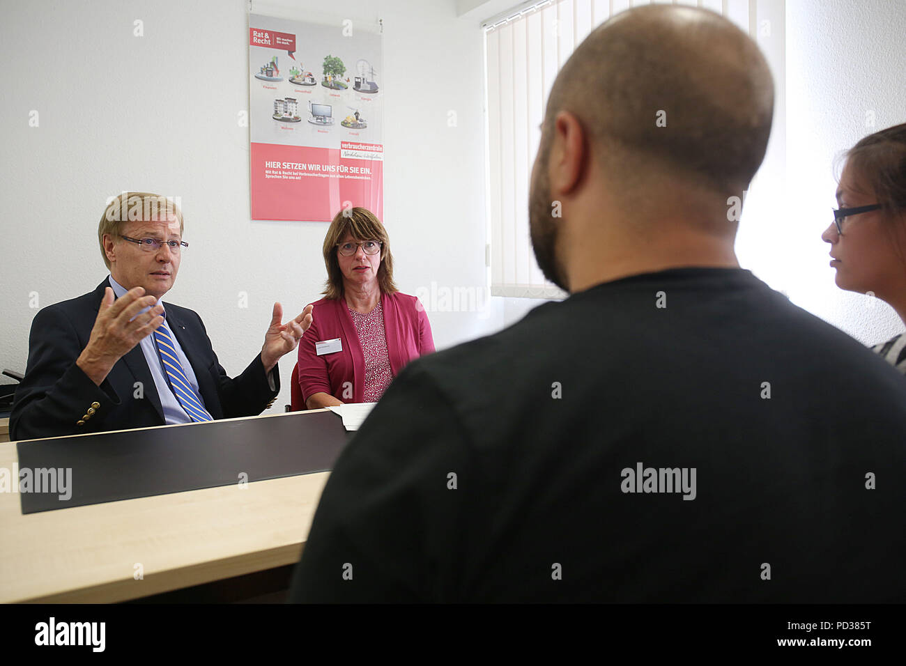 Remscheid, Germany. 06th Aug, 2018. North Rhine-Westphalia's Minister of Justice Peter Biesenbach (L) of the Christian Democratic Union (CDU), and Lydia Schwertner (2-L), head of the office of the consumer advice centre Remscheid, take part in the counselling interview with the married couple Cuma (2-R) and Sylvana (r) Eryilmaz. The Minister of Justice took part in consultations at the consumer advice centre. Credit: Oliver Berg/dpa/Alamy Live News - Stock Image