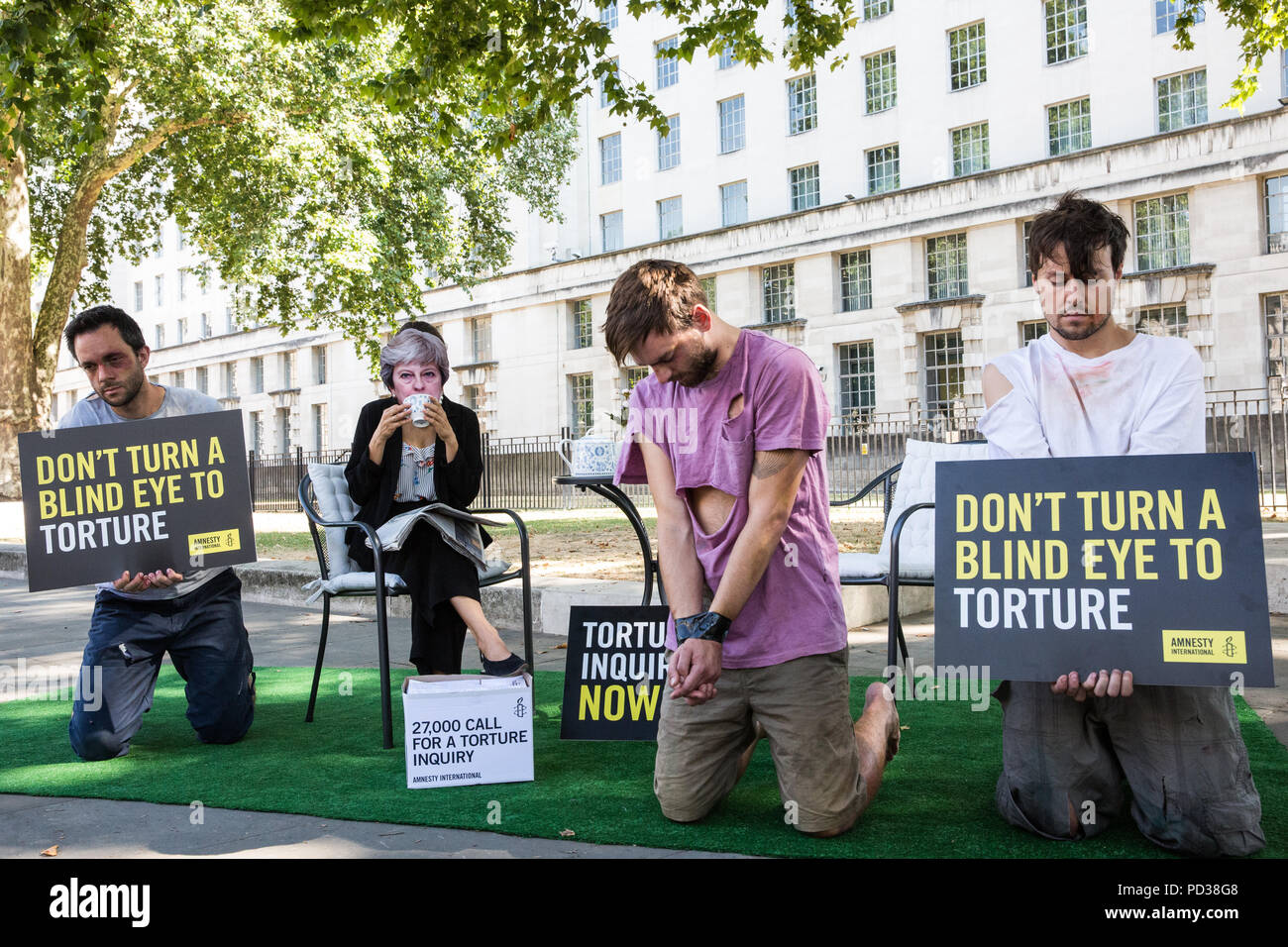London, UK. 6th August, 2018. An activist from Amnesty UK wearing a Theresa May mask drinks tea outside Downing Street while ignoring three victims of torture as part of a protest calling for an independent, judge-led inquiry into the UK's involvement in the torture of detainees overseas. A petition was also presented to 10 Downing Street by Amnesty UK Director Kate Allen, Simone Abel of Reprieve, Sam Grant of Liberty and Sonya Sceats of Freedom from Torture). Credit: Mark Kerrison/Alamy Live News Stock Photo