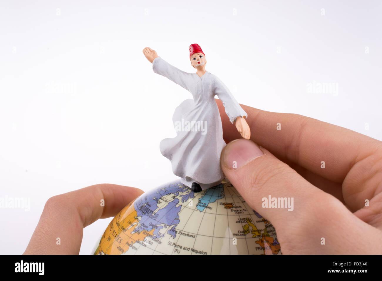 Hand holding a Sufi Derviş on a globe - Stock Image