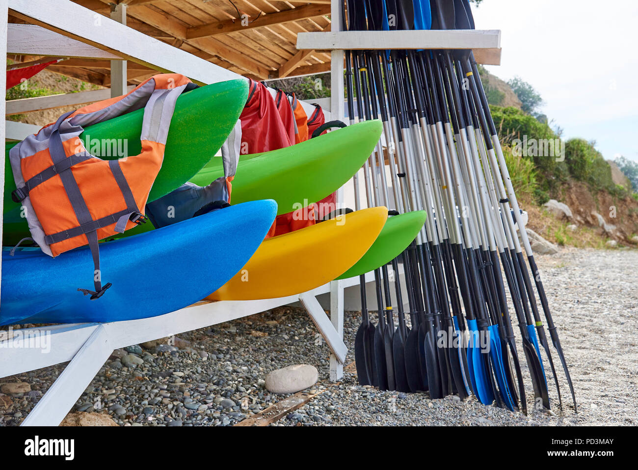 Kayaks, life jackets, oars under a wooden roof on the beach. Stock Photo