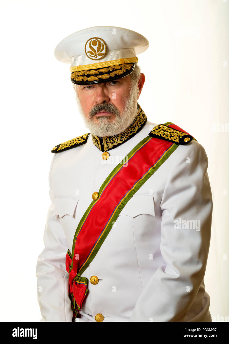 Fictional character : Governor Babala with white full uniform, red honorific sash and officer's cap, - Stock Image