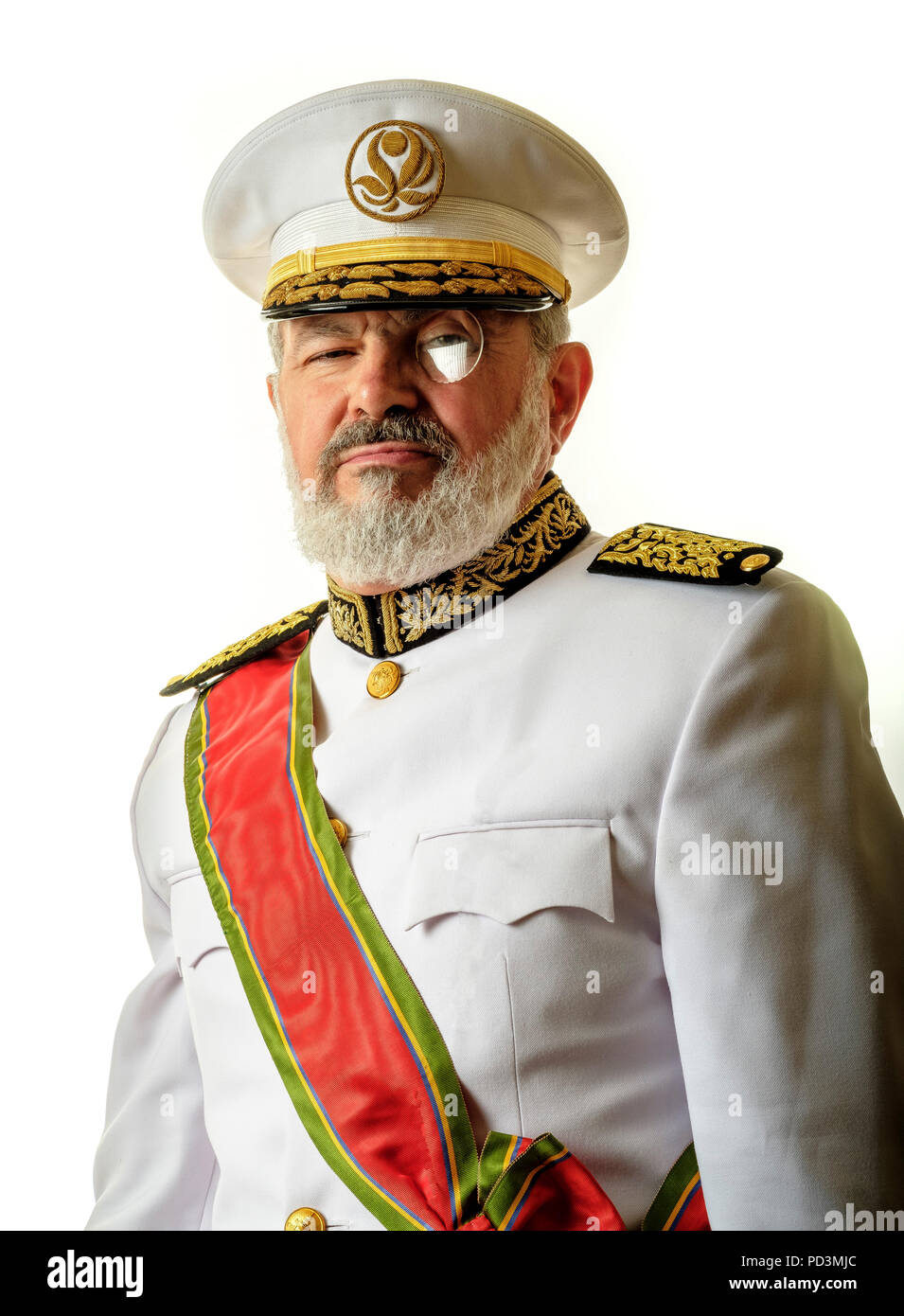 Fictional character : Governor Babala with white full uniform, red honorific sash and monocle, - Stock Image