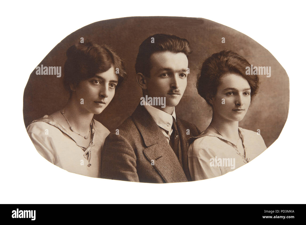 1925's vintage sepia toned picture with two sisters and brother, family portrait - Stock Image