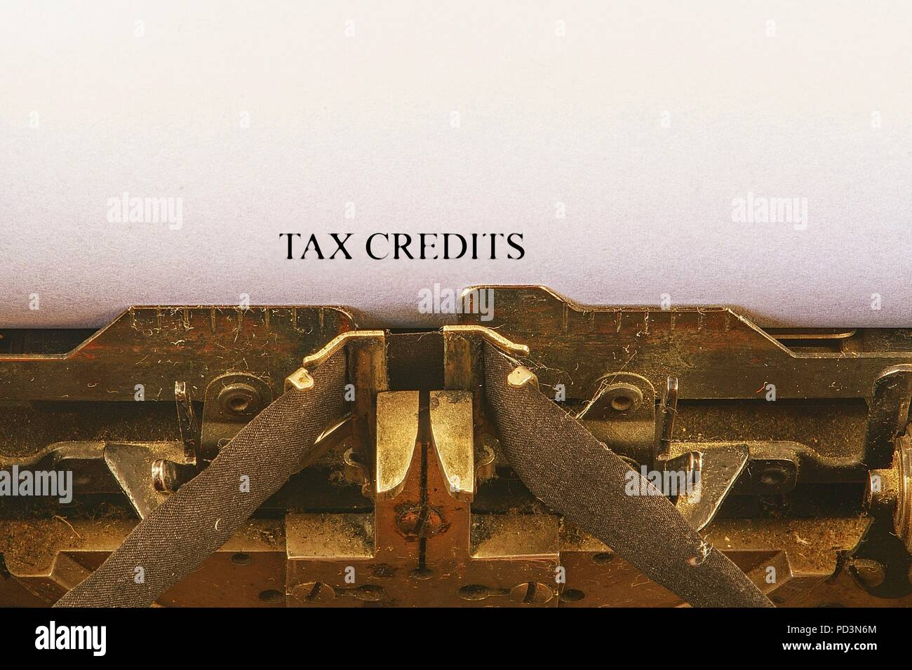 Closeup on vintage typewriter. Front focus on letters making TAX CREDITS text. Business concept image with retro office tool - Stock Image