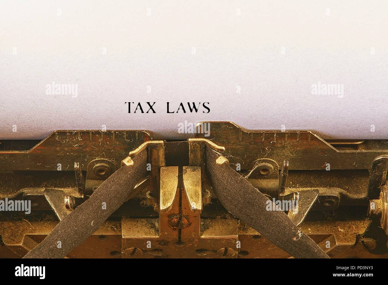 Closeup on vintage typewriter. Front focus on letters making TAX LAWS  text. Business concept image with retro office tool - Stock Image