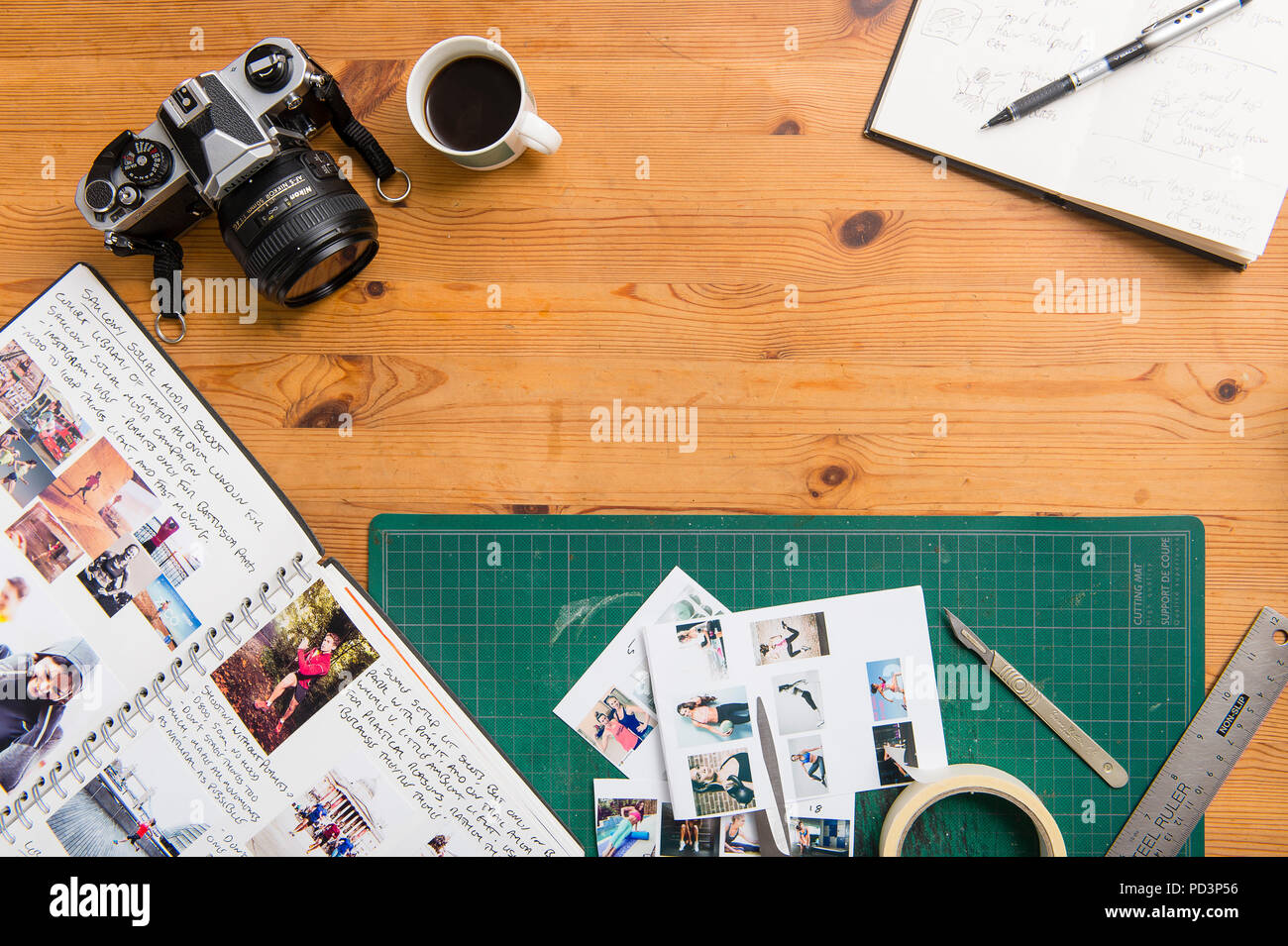 Top down view of tabletop with fiml camera, sketchbook, coffee, notebook, scalpel and cutting mat - Stock Image