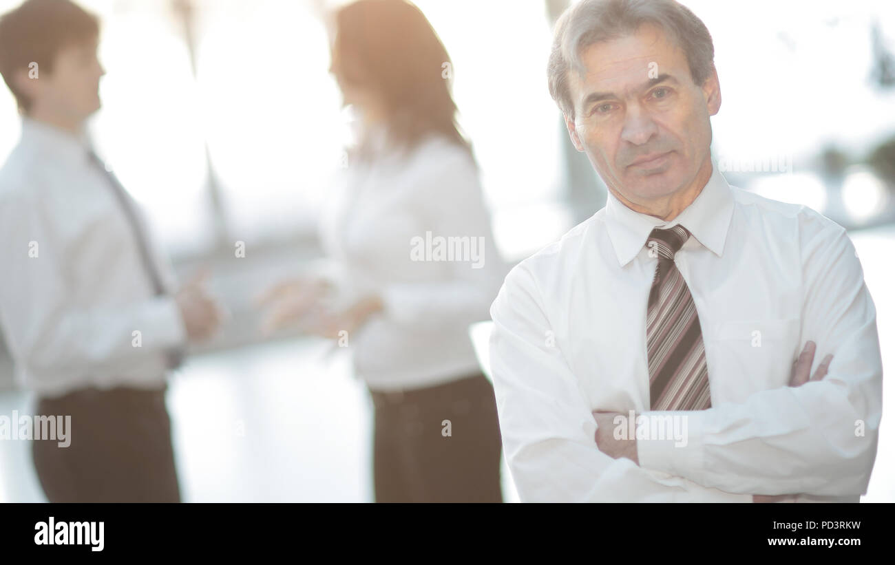 portrait of a senior businessman on blurred background office - Stock Image