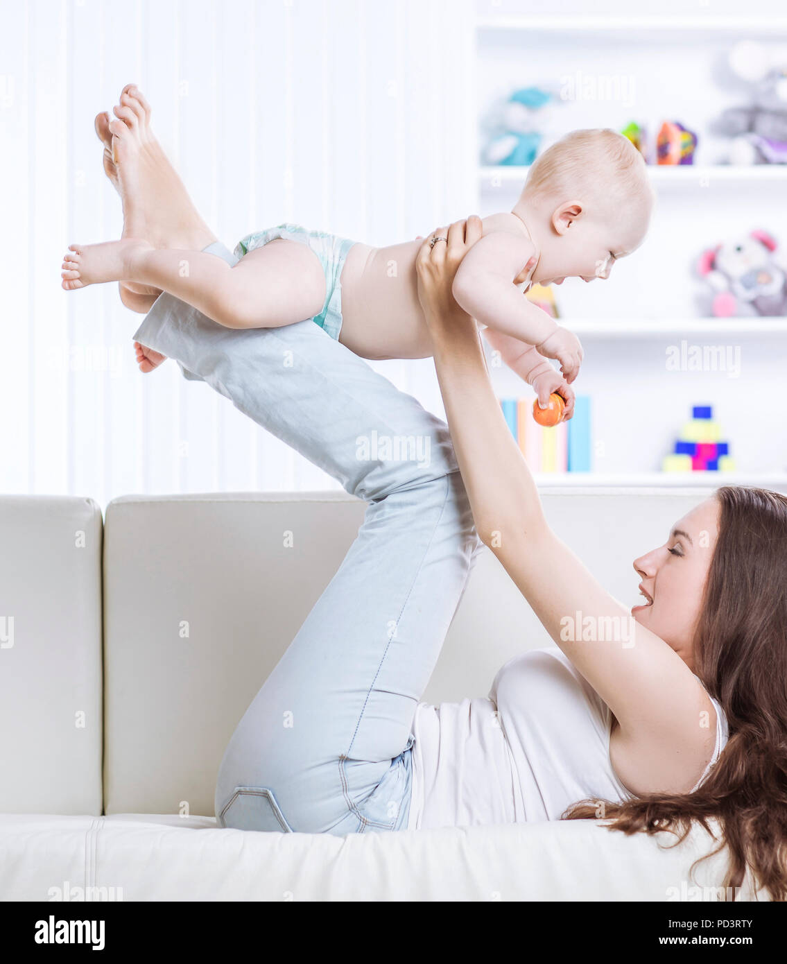 concept of happiness:happy mother playing with one year old baby in the room for children - Stock Image
