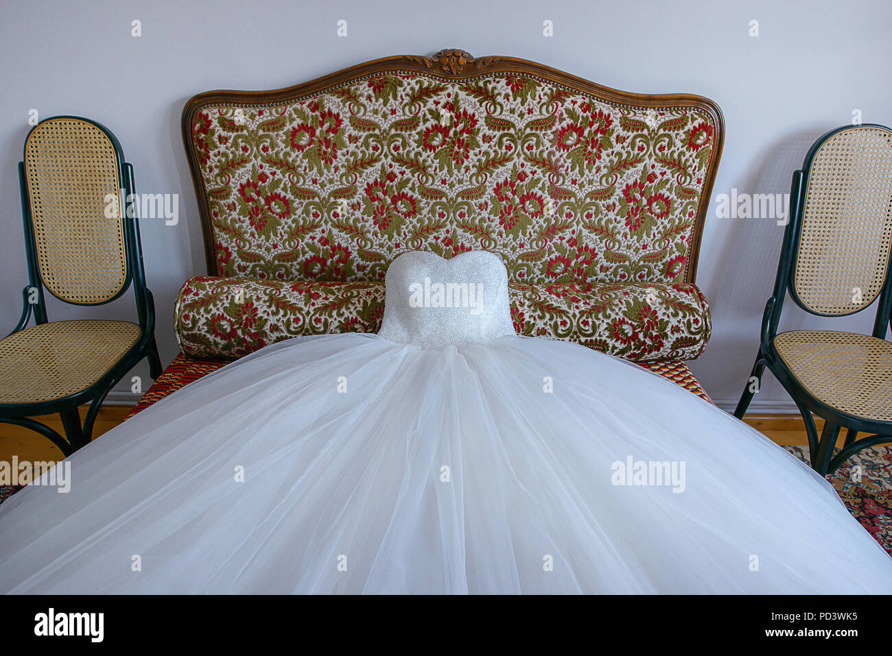 Stunning ball gown wedding dress spread on a small sofa, ready for the bride in preparation for the big day Stock Photo