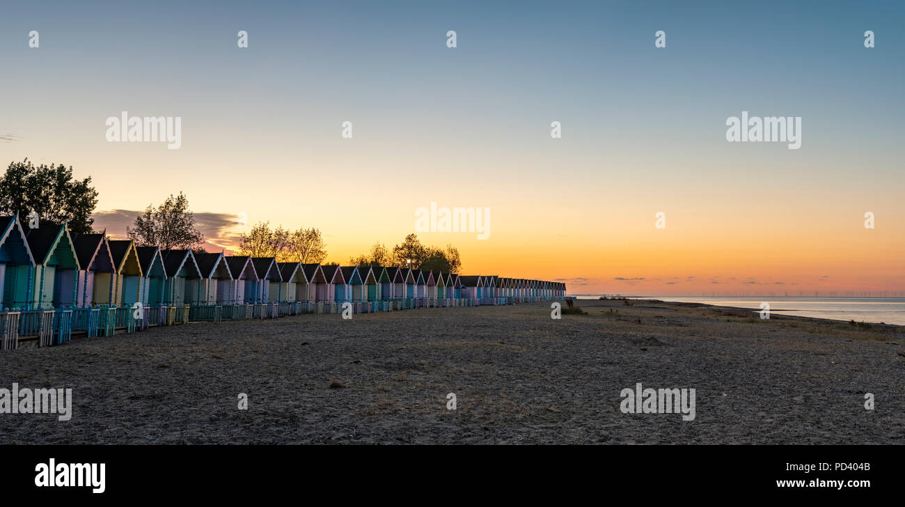Attractive Beach huts at sunrise in summer on deserted West Mersey seaside resort beach in England - Stock Image