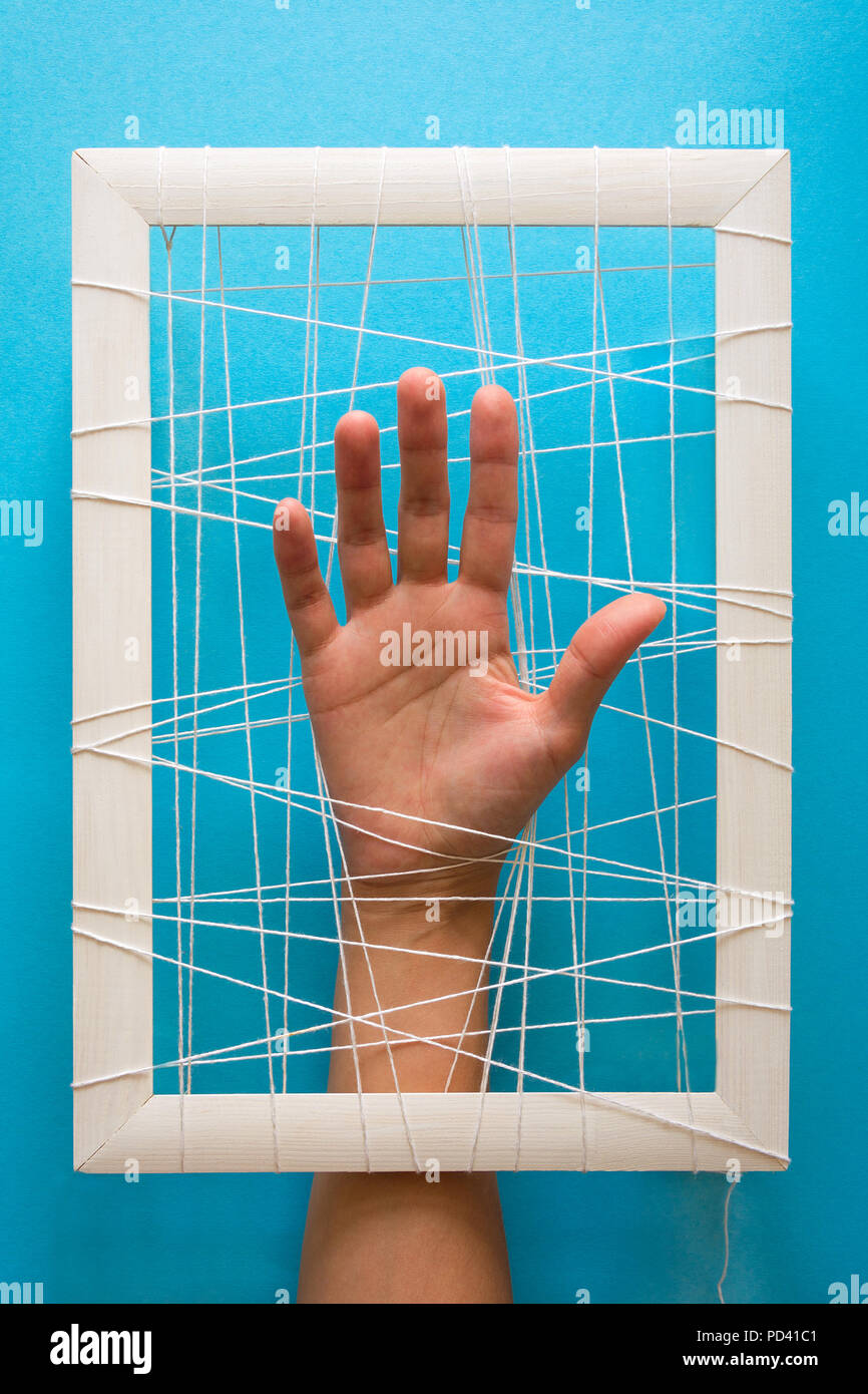 Mental health concept. Women's hands try to break the fetters on blue background - Stock Image
